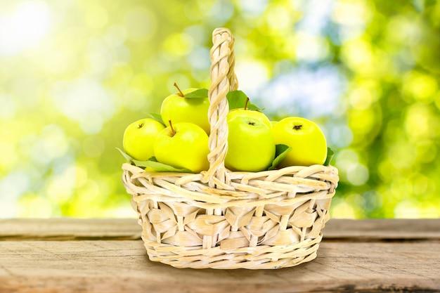 Weidenkorb mit reifen grünen äpfeln auf holztischplatte vor dem hintergrund von baumblättern.