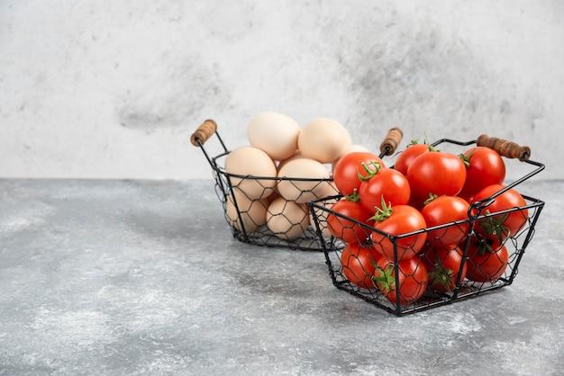 Weidenkorb mit rohen bio-eiern und roten tomaten auf marmor.
