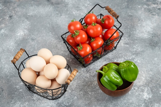Weidenkorb mit rohen bio-eiern und tomaten mit paprika auf marmor.