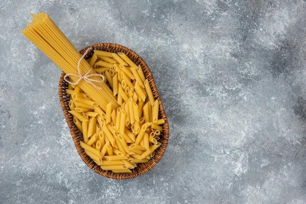 Weidenkorb mit rohen spaghetti und penne-nudeln auf marmoroberfläche.