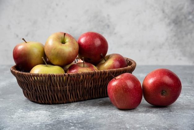 Weidenkorb mit roten saftigen äpfeln auf marmoroberfläche.