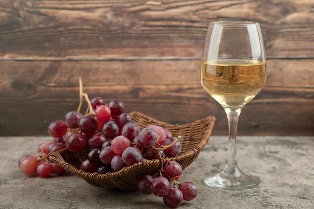 Weidenkorb mit roten trauben mit glas wein auf marmortisch.