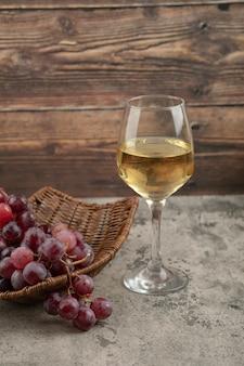 Weidenkorb mit roten trauben mit glas weißwein auf marmortisch.