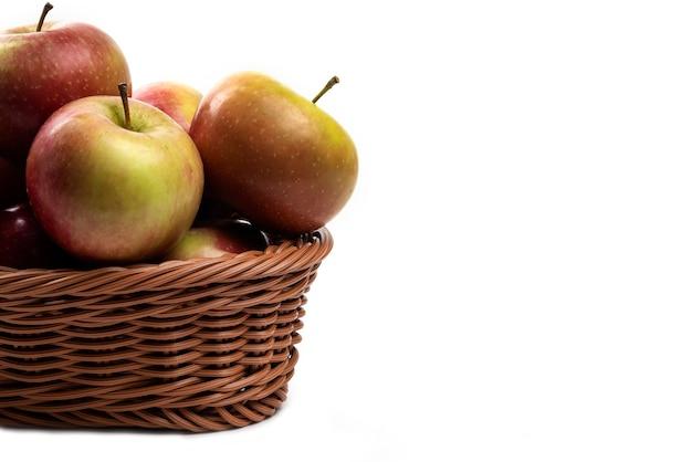 Weidenkorb von frischen saftigen äpfeln lokalisiert auf weiß.