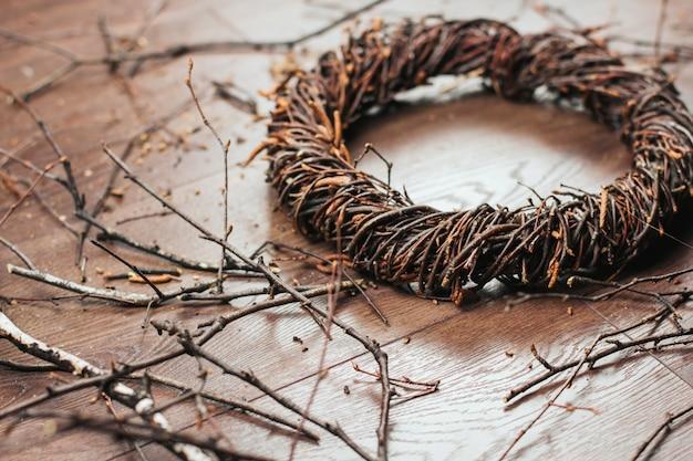 Weidenkranz von birkenzweigen auf einem hölzernen hintergrund. einen kranz aus zweigen weben.