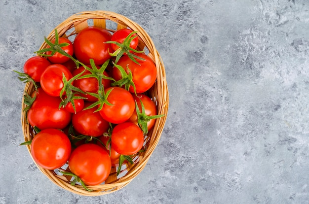 Weidenschüssel mit roten tomaten. studio-foto