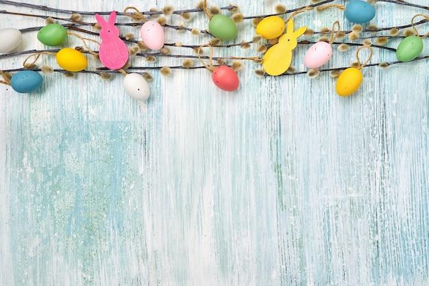 Weidenzweig und dekorative ostereier an der blauen wand. draufsicht, kopierraum