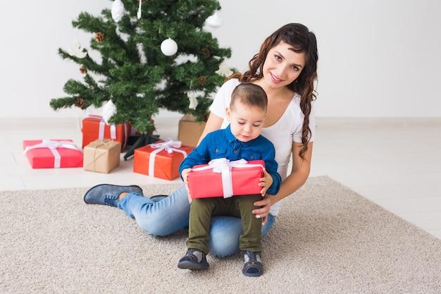 Weihnachten, alleinerziehende und feiertagskonzept - netter kleiner junge, der weihnachtsgeschenk für seine mutter zu hause hält.