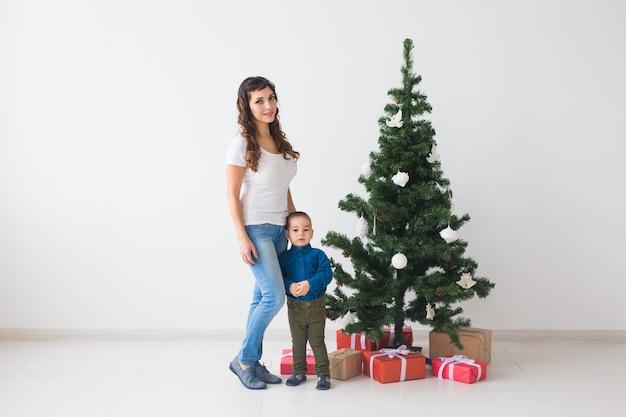 Weihnachten, alleinerziehende und feiertagskonzept - netter kleiner junge und seine mutter, die nahe weihnachtsbaum stehen.