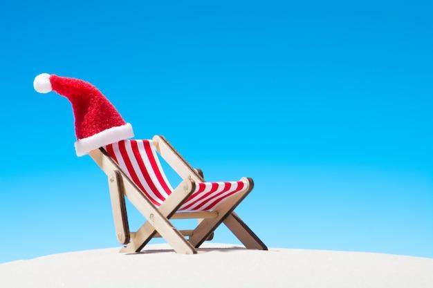 Weihnachten am strand: ein liegestuhl mit weihnachtsmütze