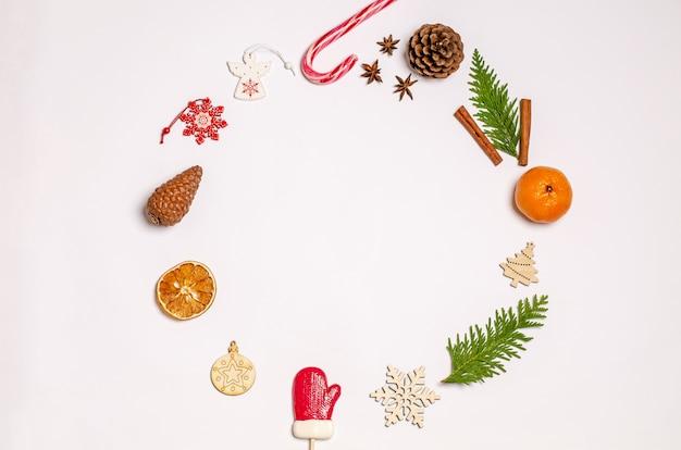 Weihnachten auf weißem hintergrund mit festlichem dekor in form eines runden rahmens aus wacholder, zimt, anis, trockenen orangen, holzspielzeug, karamellbonbons, zapfen. kopieren sie platz, flach liegen. ansicht von oben