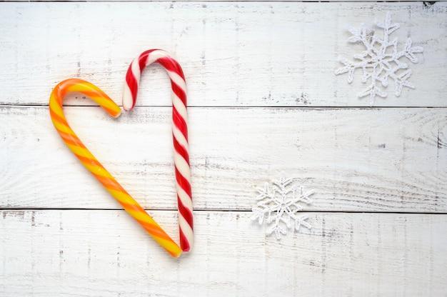 Weihnachten behandelt helle zuckerstangen in einer herzform auf weißem holzbrett