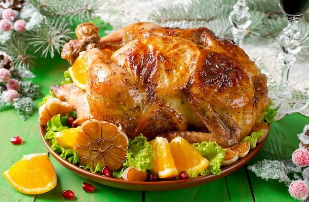 Weihnachten brathähnchen gefüllt mit orangen und dekoriert mit orangenscheiben und gebratenem knoblauch