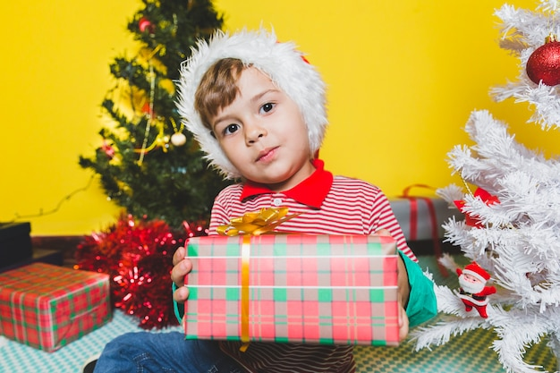 Weihnachten concepto mit dem kind, das präsentkarton hält