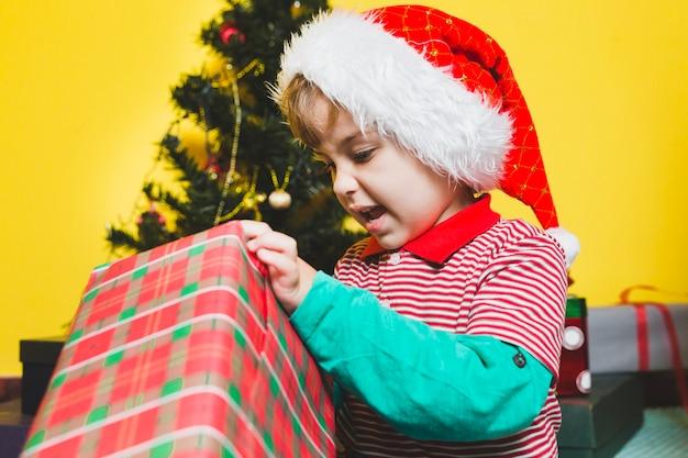 Weihnachten concepto mit jungenöffnungsgeschenk
