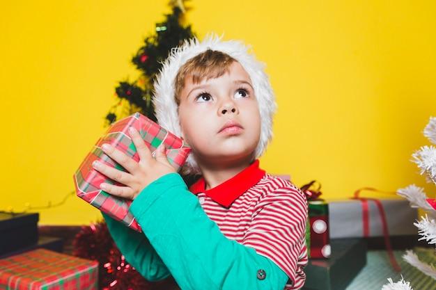 Weihnachten concepto mit mit dem jungen, der präsentkarton rüttelt