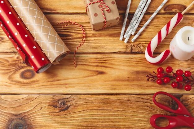 Weihnachten, das einzelteile auf hölzernem hintergrund einwickelt und verziert