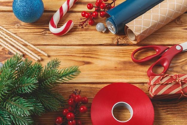 Weihnachten, das einzelteile auf hölzernem hintergrund mit kopienraum einwickelt und verziert
