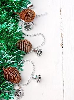 Weihnachten eine weiße hölzerne retro- weinlese girlande des feiertagsdekorations-tannenrustikalen alten kegellametta-winters von silbernen glocken