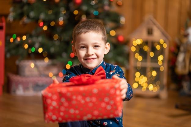 Weihnachten fabelhaft, kleiner junge, der eine große rote schachtel mit einem geschenk vom weihnachtsmann hält.