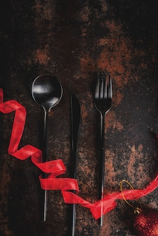 Weihnachten, feierkonzept des neuen jahres, satz tafelsilber auf einem dunklen rostigen, verziert mit rotem band und weihnachtsbaumball, draufsicht copyspace