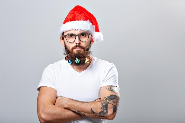 Weihnachten, feiertage, friseursalon und stilkonzept - junger gutaussehender bärtiger weihnachtsmann mit vielen kleinen weihnachtskugeln im langen bart.