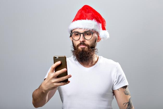 Weihnachten, feiertage, technologie und menschenkonzept - gut aussehender bärtiger mann in weihnachtsmütze, der ein selfie-foto mit smartphone auf grauem hintergrund macht.