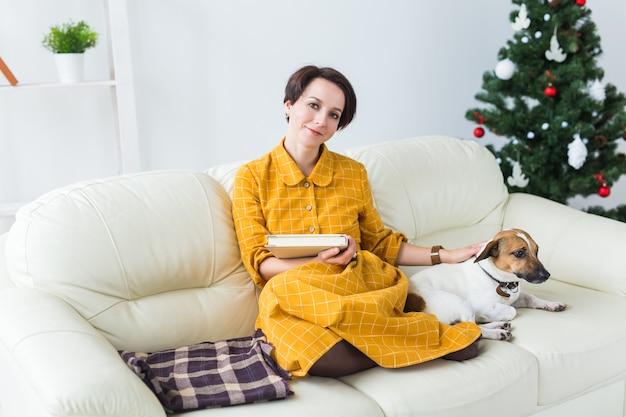 Weihnachten, feiertage und leutekonzept - glückliche junge frau, die zu hause buch liest.