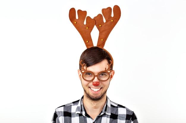 Weihnachten, feiertage und lustiges konzept - mann mit hirschhörnern und rudolf nous auf weißem hintergrund