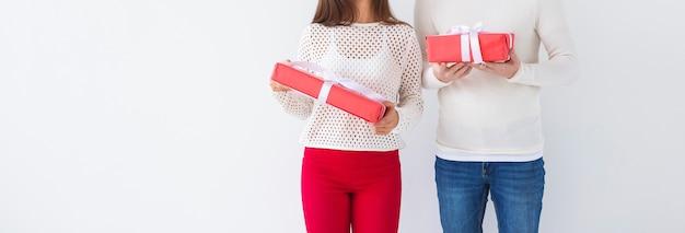 Weihnachten, feiertage, valentinstag und geburtstagskonzept - glücklicher mann und frau hält kisten mit geschenken auf weißem hintergrund mit kopienraum.