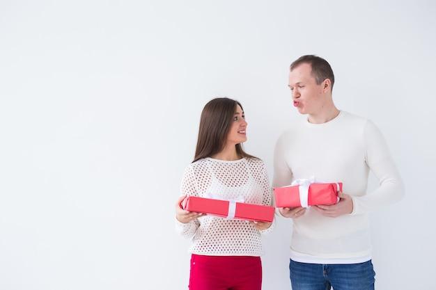 Weihnachten, feiertage, valentinstag und geburtstagskonzept - glücklicher mann und frau hält kisten mit geschenken auf weißem hintergrund mit kopierraum
