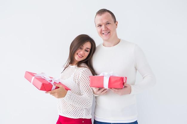 Weihnachten, feiertage, valentinstag und geburtstagskonzept - glücklicher mann und frau hält kisten mit geschenken auf weißem hintergrund