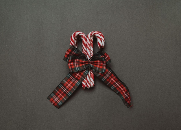 Weihnachten flach. ein bündel weihnachtskaramell-stöcke mit einer schleife. das konzept des urlaubs. platz für deinen text