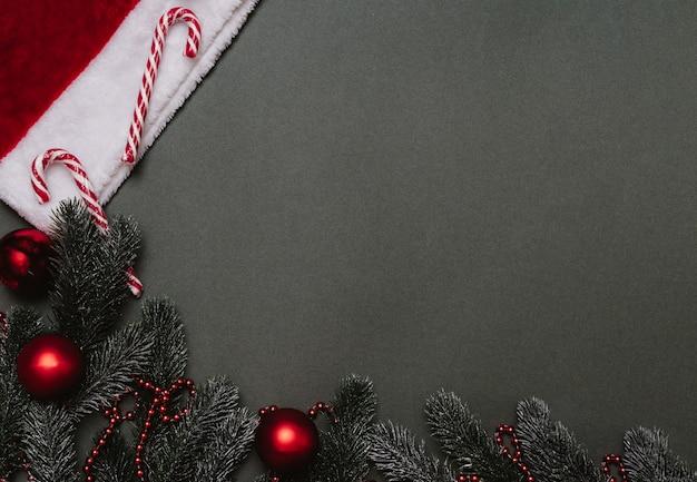 Weihnachten flach. weihnachtshintergrund aus tannenzweigen, ballons, karamellstöcken, kegeln und einer weihnachtsmütze. ein platz für ihren text oder ihre anzeige.