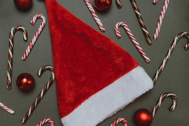 Weihnachten flach. weihnachtshintergrund aus tannenzweigen, ballons, karamellstöcken, kegeln und einer weihnachtsmütze.
