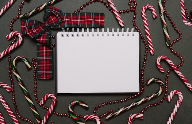 Weihnachten flach. weihnachtshintergrund von ballons, karamellstöcken, kegeln und einer weihnachtsmütze. ein platz für ihren text oder ihre anzeige.