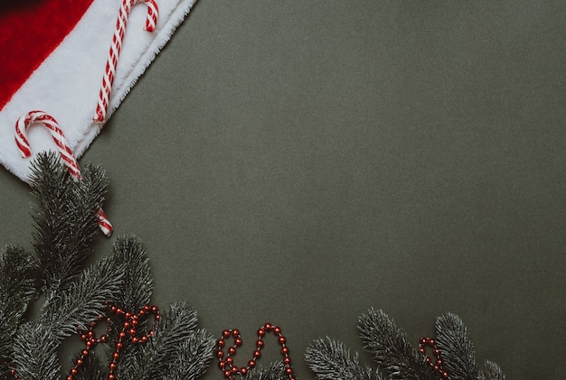 Weihnachten flach. weihnachtshintergrund von tannenzweigen, karamellstöcken, kegeln und einer weihnachtsmütze. ein platz für ihren text oder ihre anzeige.