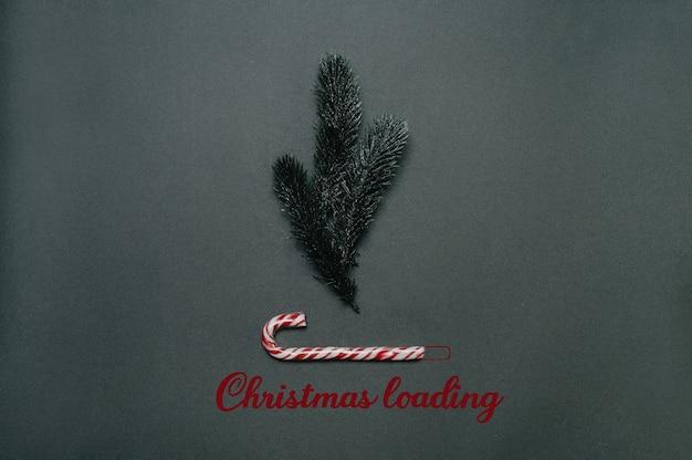 Weihnachten flach. weihnachtsladeinschrift unter tannenzweigen und karamellrohr.