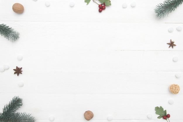 Weihnachten-frame-komposition. weihnachtsgeschenk, gewürze, nüsse, tannenzweige auf hölzernem weißem hintergrund. flache lage, draufsicht, kopienraum