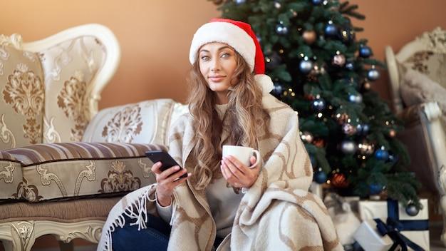 Weihnachten. frau gekleidet weißen pullover weihnachtsmütze auf dem boden in der nähe von weihnachtsbaum mit smartpone und tasse kaffee