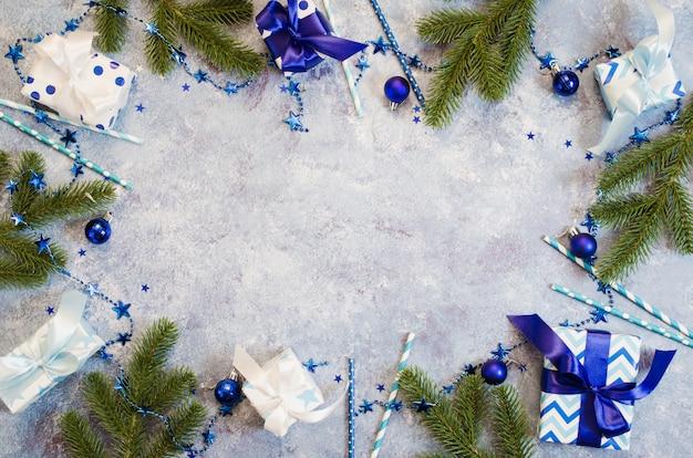 Weihnachten geschenkboxen und tannenzweige mit dekoration in blauer farbe.