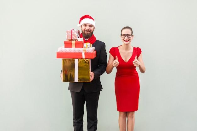 Weihnachten, geschenkkonzept. bärtiger geschäftsmann, der viele geschenkboxen für familie hält, ihre frauendaumen hoch und lächelnd. gut gekleidete paare des glücks, die kamera und zahniges lächeln betrachten. studioaufnahme