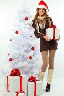Weihnachten - glückliches mädchen mit geschenk und schneetanne auf weißem hintergrund