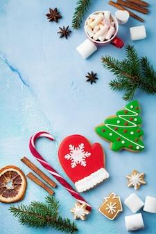 Weihnachten. gruppe von lebkuchen, zimt, orange, spielzeug und tasse heißer schokolade auf hellblau.