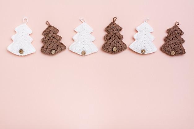 Weihnachten handgemacht. gestrickte tannen in einer reihe auf pastellfarbenem hintergrund. handwerk und freizeit. speicherplatz kopieren