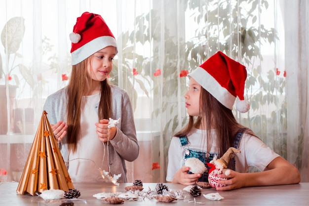 Weihnachten handgemacht. mädchen machen einen weihnachtsbaum aus papier und schmücken ihn.