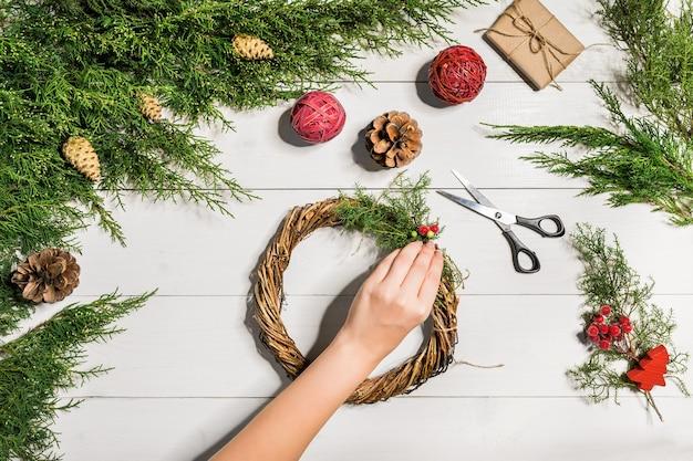 Weihnachten handgemachte diy hintergrund. basteln sie weihnachtskranz und ornamente. freizeit der frau, werkzeuge und schmuckstücke für feiertagsdekorationen. draufsicht auf weißen holztisch mit weiblichen händen.