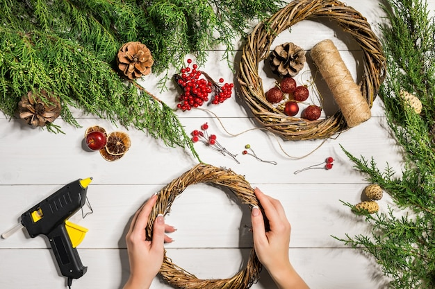 Weihnachten handgemachte diy hintergrund machen handwerk weihnachtskranz und ornamente draufsicht auf weiße holzta...