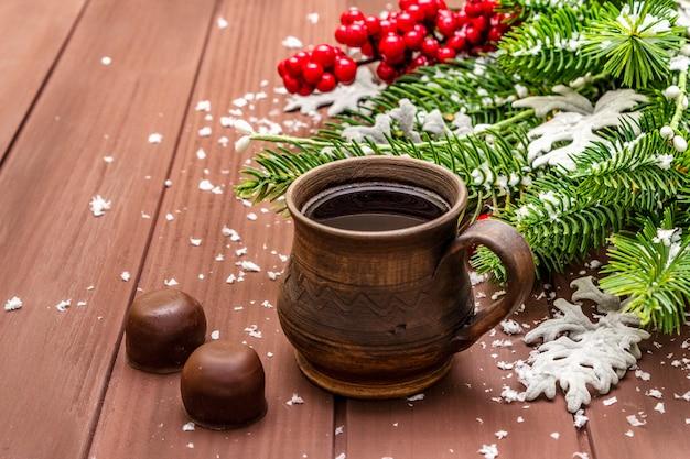 Weihnachten heißen kaffee. tannenbaum des neuen jahres, heckenrose, frische blätter, pralinen und künstlicher schnee.