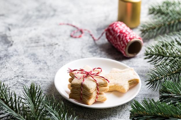Weihnachten hintergrund. festliches lebkuchenplätzchen mit band, kiefernzweige